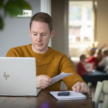 Rob, living with blood cancer, working at his laptop at home