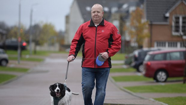 Derek, in remission from blood cancer, walking his dog