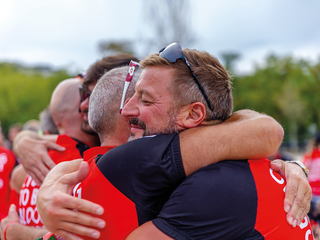 Bloodwise supporters hugging at a sports event.png