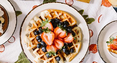 A brunch spread including fruit and waffles