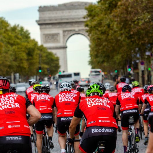 Cyclists at the Bloodwise London to Paris ride approach the Arc De Triumph