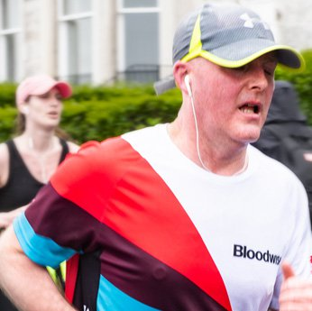 Older man running in a Bloodwise shirt at the Brighton Marathon