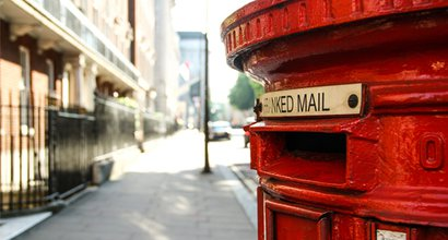 A red London postbox on a city street
