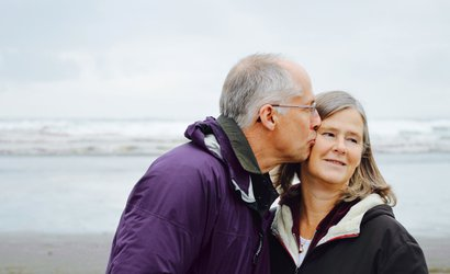 Affectionate older couple going for a walk by the sea