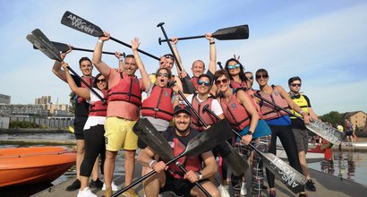The itsu team at the Dragon Boat race pose together with oars held aloft.