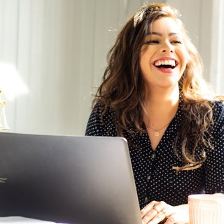 A woman laughing at her desk, alongside a computer