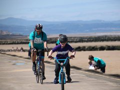 An adult and child rider together at the North Wales Coast Bikeathon