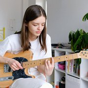 Woman playing guitar for homepage
